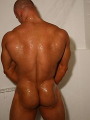Muscular guy posing in shower