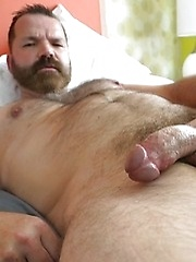 Bearded Daddy Rob Hunter strips naked and strokes his thick cock for the camera